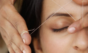 Woman getting eyebrow threading treatment in Hyde